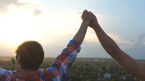 Friends run up to edge of roof and jump showing joyful emotions. Gay couple raising hands and rejoicing life together at. Sunset time. Beautiful view. Slow stock video footage
