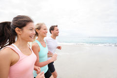 Friends runners jogging on beach. Group running on beach jogging having fun training. Exercising runners training outdoors living healthy active lifestyle Royalty Free Stock Photos