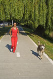 Friends running. Young woman and her dog running in the morning Stock Photos
