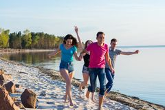 Friends are running along the seashore, holding hands and laughing. Young people, boys and girls, students are happy on the beach stock image