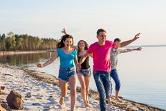 Friends are running along the seashore, holding hands and laughi. Ng. Young people, boys and girls, students are happy on the beach Royalty Free Stock Photo