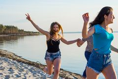 Friends are running along the seashore, holding hands and laughi. Ng. Young people, guy and girls, students are happy on the beach Stock Photography