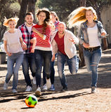 Friends running with ball Royalty Free Stock Photography