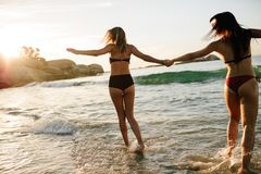 Friends running on the beach and having fun. Rear view of two girl friends running on the beach and having fun. Women in bikini holding hands and running on sea Stock Images