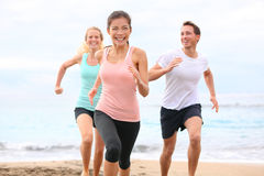 Friends running on beach jogging. Group running on beach jogging having fun training. Exercising runners training outdoors living healthy active lifestyle Royalty Free Stock Image