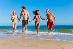 Friends running on beach vacation. Four friends - men and women - on the beach having lots of fun in their vacation running through the water Stock Image