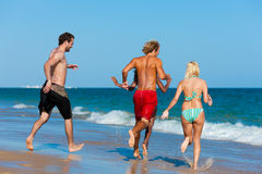 Friends running on beach vacation Stock Photos