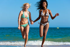 Friends running on beach vacation Stock Image