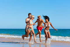 Friends running on beach vacation Stock Photography