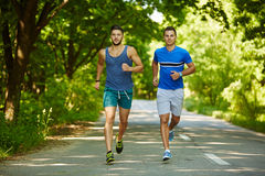 Friends running through forest Stock Images