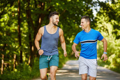 Friends running through forest Royalty Free Stock Photos