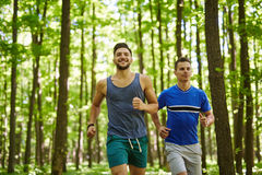 Friends running through forest Stock Photo