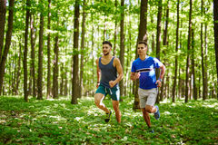 Friends running through forest Stock Photography