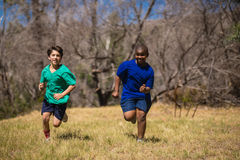 Friends running on grass during obstacle course. In boot camp royalty free stock photos