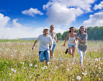 Friends running in meadow Stock Photography