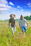 Friends running at meadow Royalty Free Stock Images