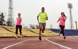 Friends running on sport ground stock photos
