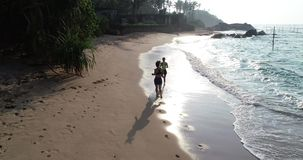 Friends running on tropical beach stock footage