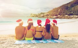 Friends in santa hats on beach at christmas. Christmas, travel, winter holidays and people concept - group of friends in santa helper hats sitting over tropical Stock Photo