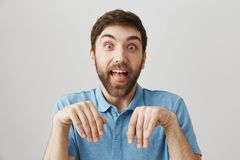 Friends say his girlfriend tamed him like dog. Funny european boyfriend with beard making dumb face, sticking out tongue. And standing with folded hands over Royalty Free Stock Photos