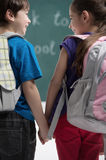 Friends at school class. Rear view of classmates holding hands a Stock Photos