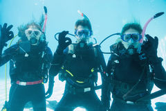 Friends on scuba training submerged in swimming pool looking to camera Royalty Free Stock Photos