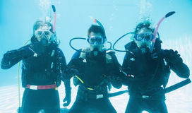 Friends on scuba training submerged in swimming pool making ok sign Royalty Free Stock Photo