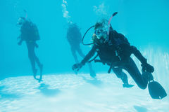 Friends on scuba training submerged in swimming pool one looking to camera Royalty Free Stock Images