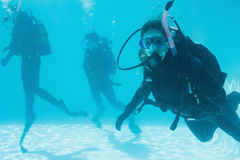 Friends on scuba training submerged in swimming pool one looking to camera Stock Photo