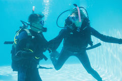 Friends on scuba training submerged in swimming pool Stock Photo