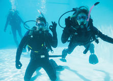 Friends on scuba training submerged in swimming pool two looking to camera Stock Photography