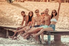 Friends on the sea. Happy friends are splashing water, looking at camera and smiling while sitting on pier at the sea royalty free stock images