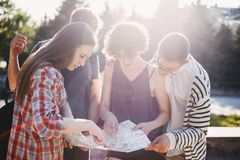 Friends searching the location on map. Traveling, sightseeing, group travel, city tour, student exchange program, vacation, holiday. Friends searching the Royalty Free Stock Image
