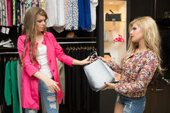 Friends are seeking for a dress at the clothes. Friends are seeking for a dress at the ready-made clothes shop Stock Image