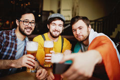 Friends Selfie in Irish Pub. Portrait of three men, one of them wrapped in Irish banner, meeting over craft beer in pub and posing for selfie shot Royalty Free Stock Photo