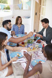 Friends serving each other at a dinner party on a patio Stock Image