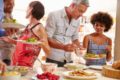 Friends serving themselves food and talking at dinner party Stock Photos