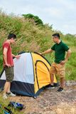 Friends setting up tent stock photography