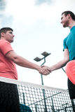 Friends shaking hands in paddle tennis Stock Photos