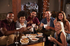 Friends sharing a Chinese take-away at home look to camera Royalty Free Stock Photo