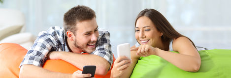 Friends sharing media content on line on phones. Two happy friends sharing media content on line with their smart phones lying on colorful puff in a house Royalty Free Stock Images