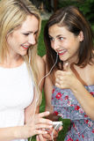Friends sharing a music player Stock Photography