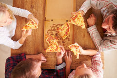 Friends sharing a pizza together, overhead view Stock Photography