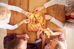 Friends sharing a pizza together, overhead view Stock Image