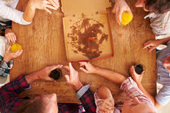 Friends sharing a pizza together, overhead view Royalty Free Stock Photography