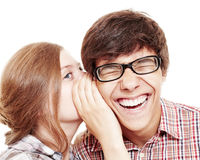 Friends sharing secrets. Pretty girl whispering secret in ear of her laughing friend isolated on white background - friendship concept Royalty Free Stock Image