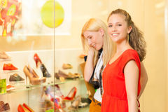 Friends shoe shopping in a mall. Or shop having fun stock images