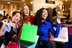 Friends shopping with bags in mall. Group of three women - white, black and Asian - shopping downtown in a mall stock photography