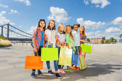 Friends with shopping bags walk arm-in-arm in city Stock Photo