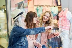 Friends shopping in front of a boutique. Group of female friends shopping in front of a fashion boutique stock images